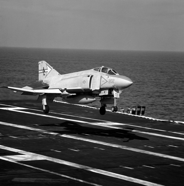 A right side view of an F-4J Phantom II aircraft from Fighter Squadron 103 (VF-103) assigned to Carrier Air Wing 3 (CVW-3) landing aboard the aircraft carrier USS SARATOGA (CV-60) underway off the coast of Florida