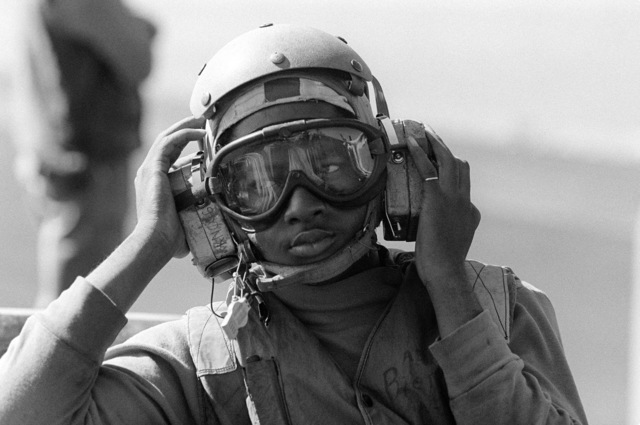 A flight deck crewman adjusts his ear protection gear while participating in flight operations aboard the aircraft carrier USS KITTY HAWK (CV 63)
