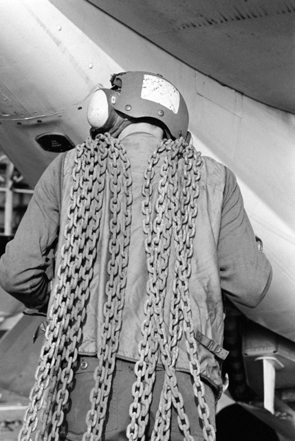 A flight deck crewman carries tie-down chains to secure aircraft aboard the aircraft carrier USS KITTY HAWK (CV 63)