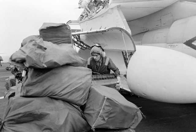A flight deck crewman offloads cargo from a US-3A Viking aircraft aboard the aircraft carrier USS MIDWAY (CV 41)