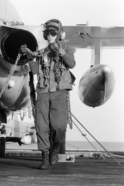 A flight deck crewmen uses tie-down chains to secure an A-6 Intruder aircraft aboard the aircraft carrier USS KITTY HAWK (CV 63)