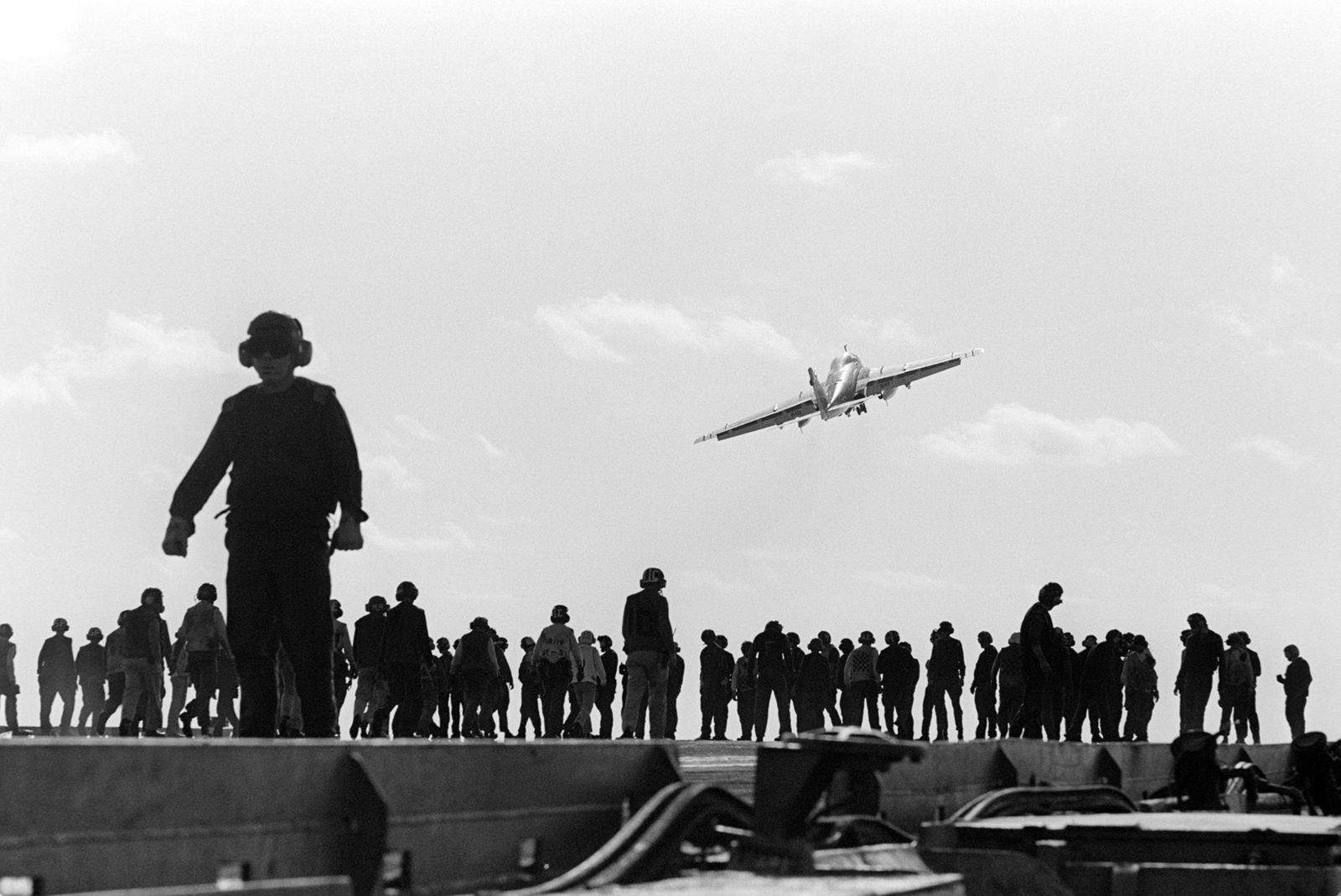 A silhouetted view of crewmen on the flight deck of the aircraft carrier USS KITTY HAWK (CV 63), as they participate in a search for foreign object damage. Visible in the background is an A-6 Intruder in flight