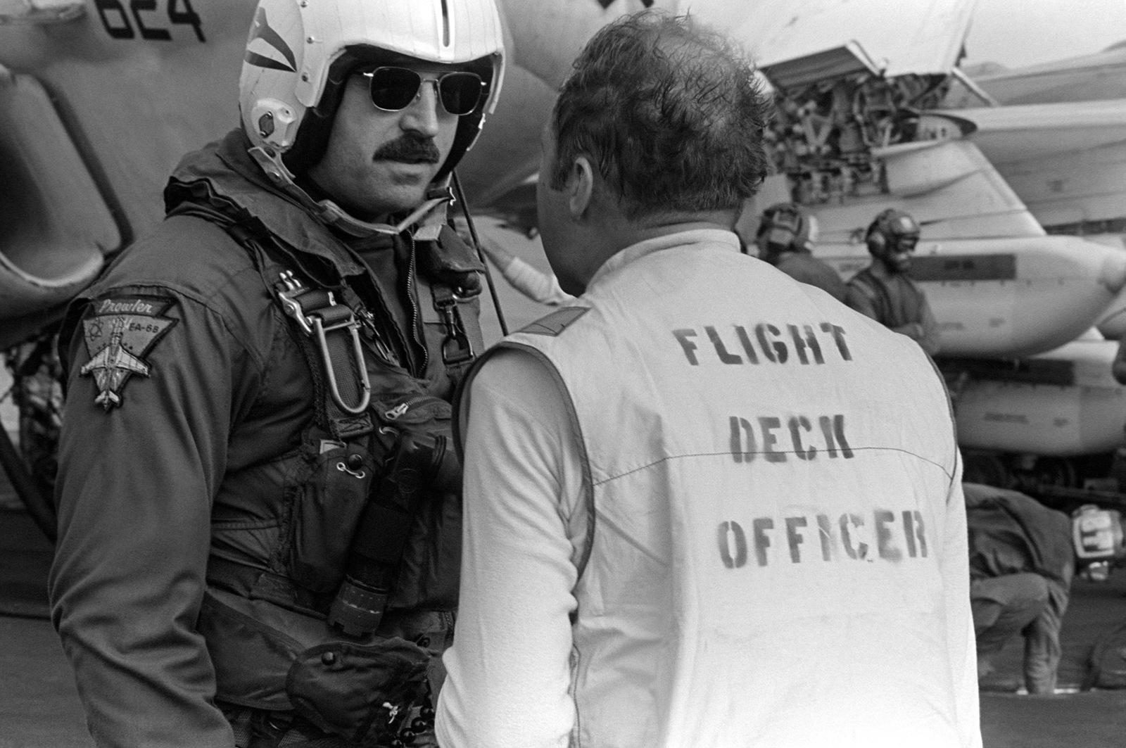 An A-6 Intruder aircraft pilot and the flight deck officer discuss