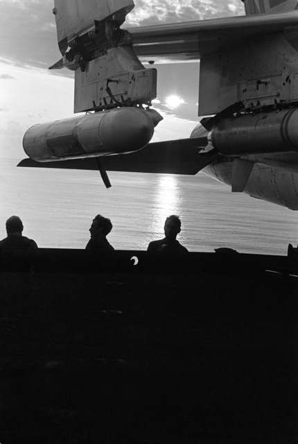 Crewmen aboard the aircraft carrier USS KITTY HAWK (CV 63) are silhouetted by the sun as they stand under an A-6 Intruder aircraft. Inert bombs are attached to the wing pylons