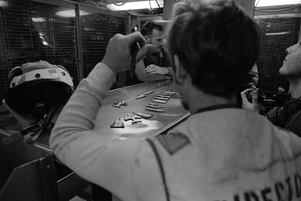 Crewmen inside the flight deck center aboard the aircraft carrier USS KITTY HAWK (CV 63) use a table to simulate the arrangement of aircraft on the carrier's flight deck