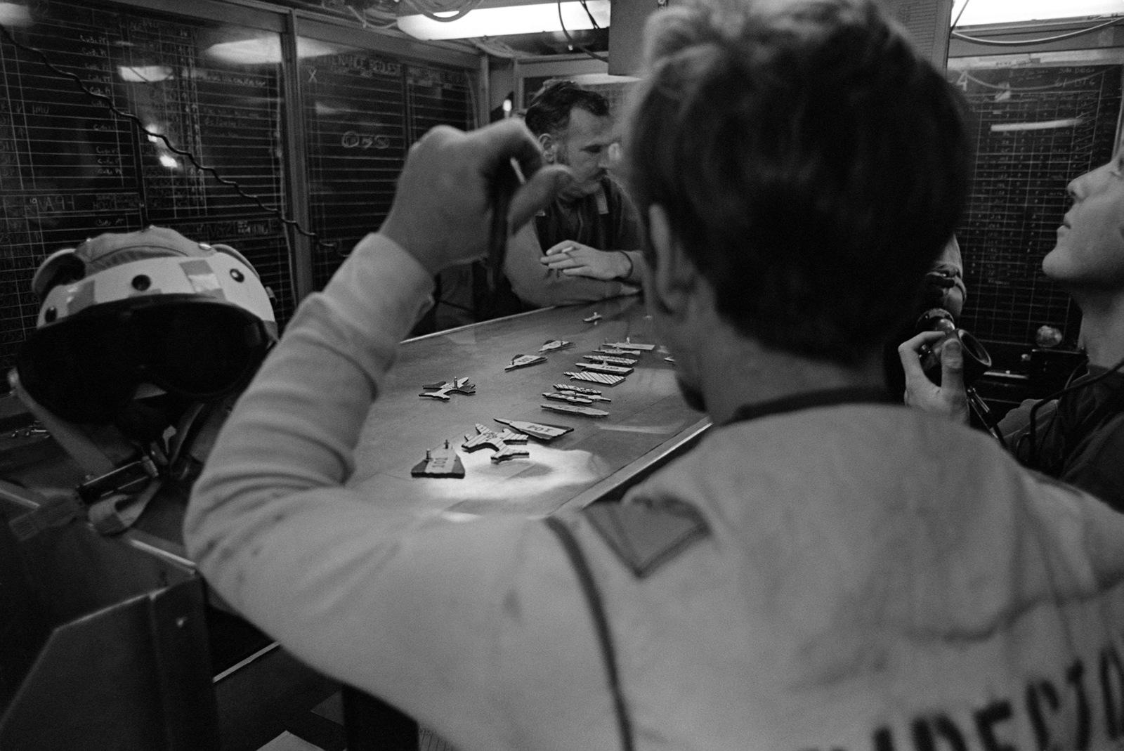 Crewmen inside the flight deck center aboard the aircraft carrier USS KITTY HAWK (CV 63) use a table to simulate the arrangement of aircraft on the carrier's flight deck