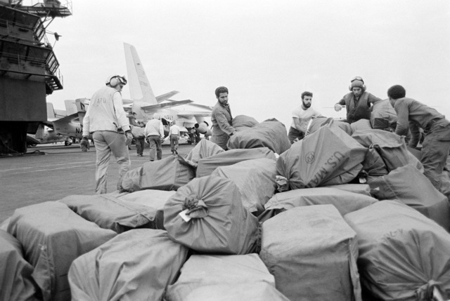 Crewmen stack cargo on the flight deck of the aircraft carrier USS MIDWAY (CV 41) after it was off loaded from a US-3A Viking aircraft