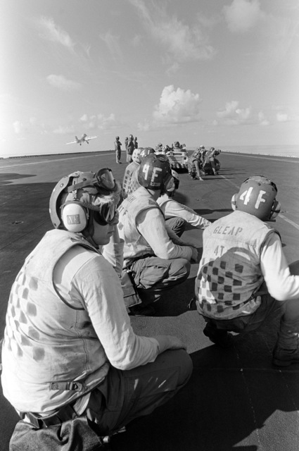 Flight deck crewmen crouch low as an A-6 Intruder aircraft is launched from the aircraft carrier USS KITTY HAWK (CV 63)