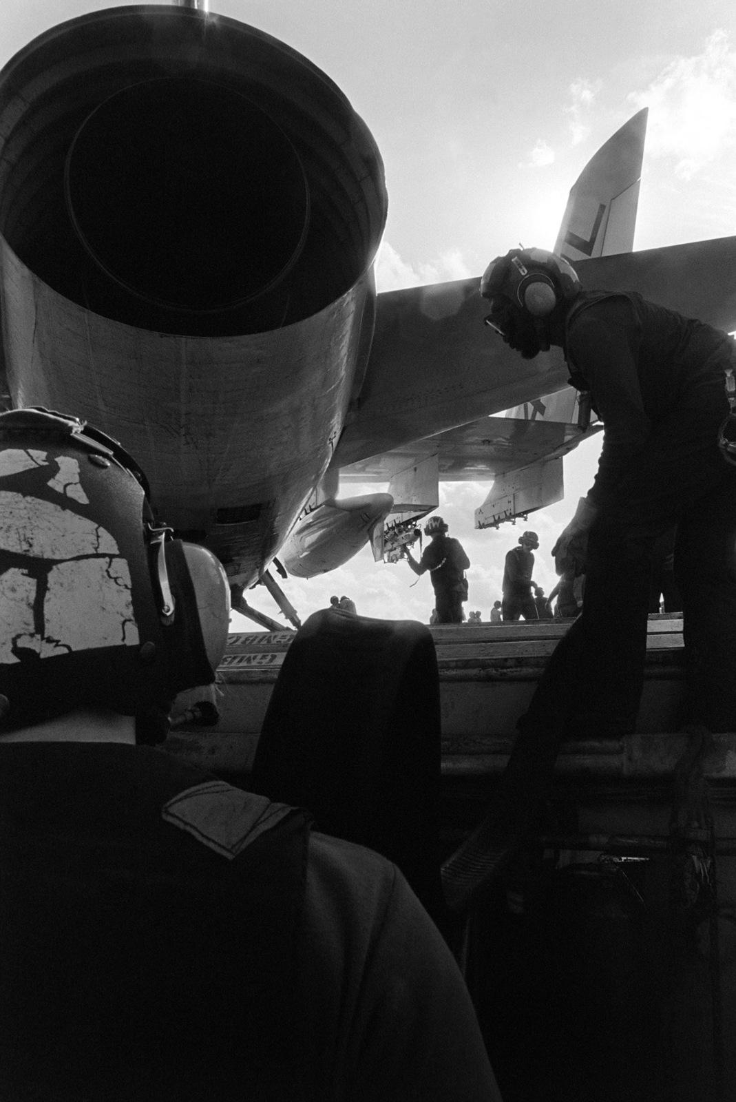 Flight deck crewmen refuel an A-7 Corsair II aircraft aboard the aircraft carrier USS KITTY HAWK (CV 63)