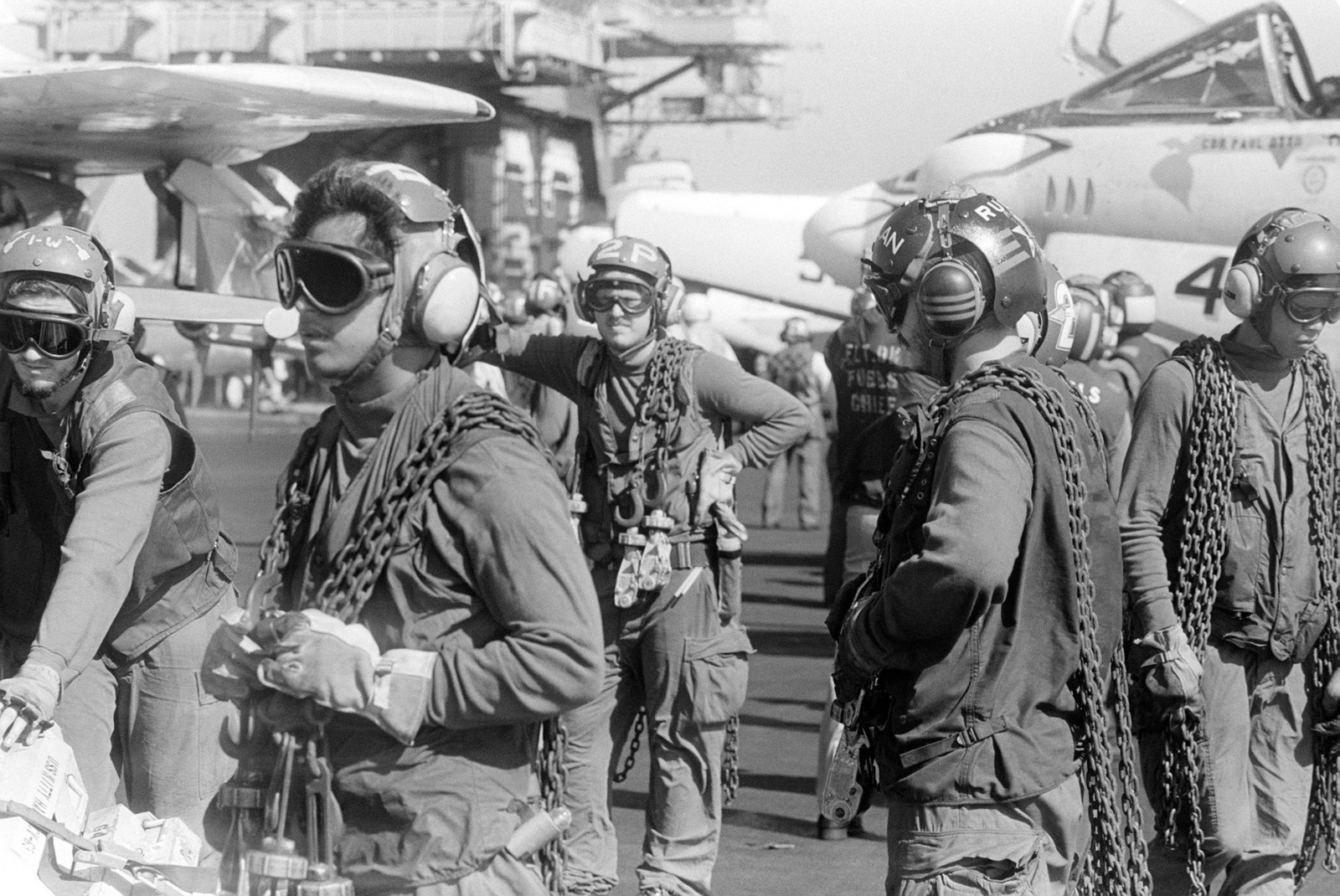 Flight deck crewmen stand by with tie down chains aboard the aircraft carrier USS KITTY HAWK (CV 63). The chains are used to secure aircraft in position on the flight deck
