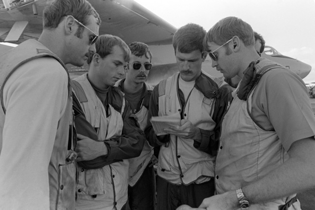Landing signal officers discuss operates on the flight deck of the aircraft carrier USS KITTY HAWK (CV 63)