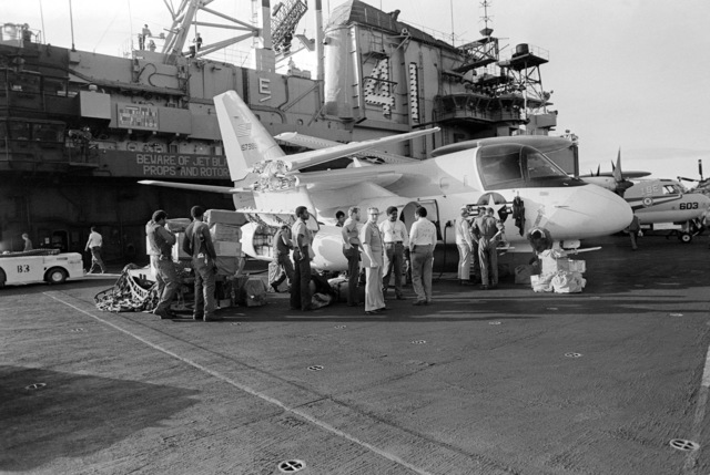 Passengers wait to go aboard a US-3A Viking aircraft on the flight deck of the aircraft carrier USS MIDWAY (CV 41). The aircraft will be transporting them to the US Naval Support Activity, Diego Garcia