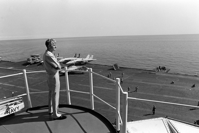 Rear Admiral (RADM) Robert E. Kirksey, commander, Task Force 77, observes flight deck operations from the 0-10 level aboard the aircraft carrier USS KITTY HAWK (CV 63)