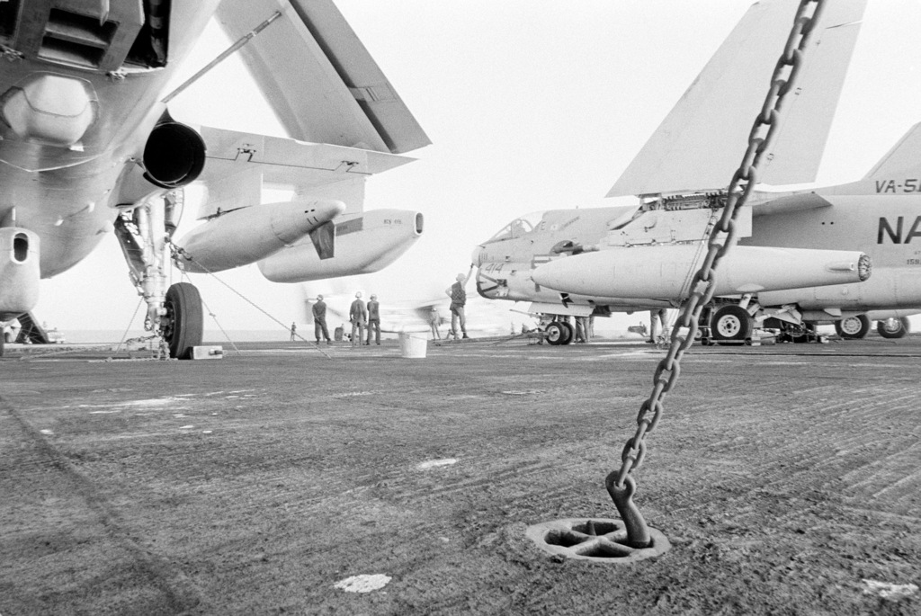 Two flight deck crewmen use tie-down chains to secure aircraft to the flight deck aboard the aircraft carrier USS KITTY HAWK (CV 63). The aircraft at right is an A-7 Corsair II and the aircraft on the left is an A-6 Intruder