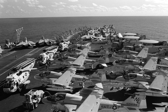 Various aircraft parked in formation aboard the aircraft carrier USS KITTY HAWK (CV 63), include A-6 Intruders, foreground, F-14 Tomcats and A-7 Corsair IIs, background, SH-3 Sea King helicopters, left, E-2C Hawkeyes and EA-6B Prowlers, right