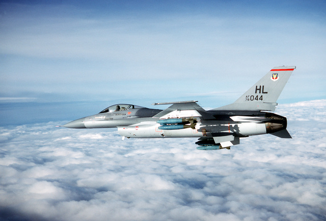 AN air-to-air left side view of an F-16 Fighting Falcon aircraft carrying 500-pound practice bombs