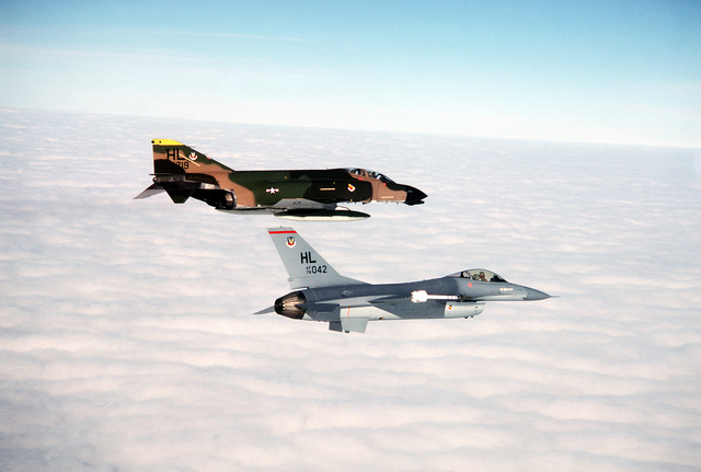 AN air-to-air right side view of an F-16 Fighting Falcon aircraft and an F-4 Phantom II aircraft in formation