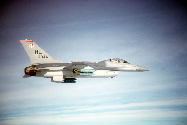 AN air-to-air right side view of an F-16 Fighting Falcon aircraft armed with 500-pound practice bombs