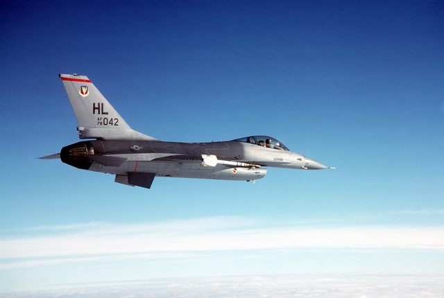 AN air-to-air right side view of an F-16 Fighting Falcon aircraft carrying AIM-9 Sidewinder missiles