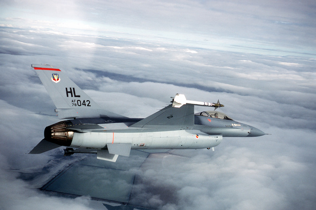 AN air-to-air right side view of an F-16 Fighting Falcon aircraft carrying AIM-9 Sidewinder missiles, banking to the right