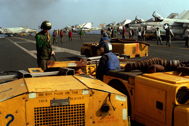 Three crewmen stand by with two MD-3 tow tractors (right) and an NC-2 Mobile Electric Powerplant (left) during flight deck operations aboard the aircraft carrier USS CORAL SEA (CV-43). In the background is an F-4 Phantom II aircraft from Marine Fighter Attack Squadron 531 (VMFA-531) (left) and A-7 Corsair II and A-6 Intruder aircraft are parked on the right