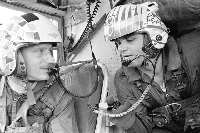 Lieutenant Commander Gregory Netzorg, left, a pilot, and Aviation Structural Mechanic 1ST Class (AM1) Garland Hatley in the cockpit of a CH-46 Sea Knight helicopter on the flight deck of the combat stores ship USS SAN JOSE (AFS 7)