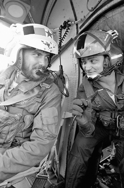 Lieutenant Junior Grade Michael G. Hegland, left, a pilot, and Aviation Structural Mechanic (Hydraulics) 2nd Class (AMH2) Gery Contreras in the cockpit of a CH-46 Sea Knight helicopter on the flight deck of the combat stores ship USS SAN JOSE (AFS 7)