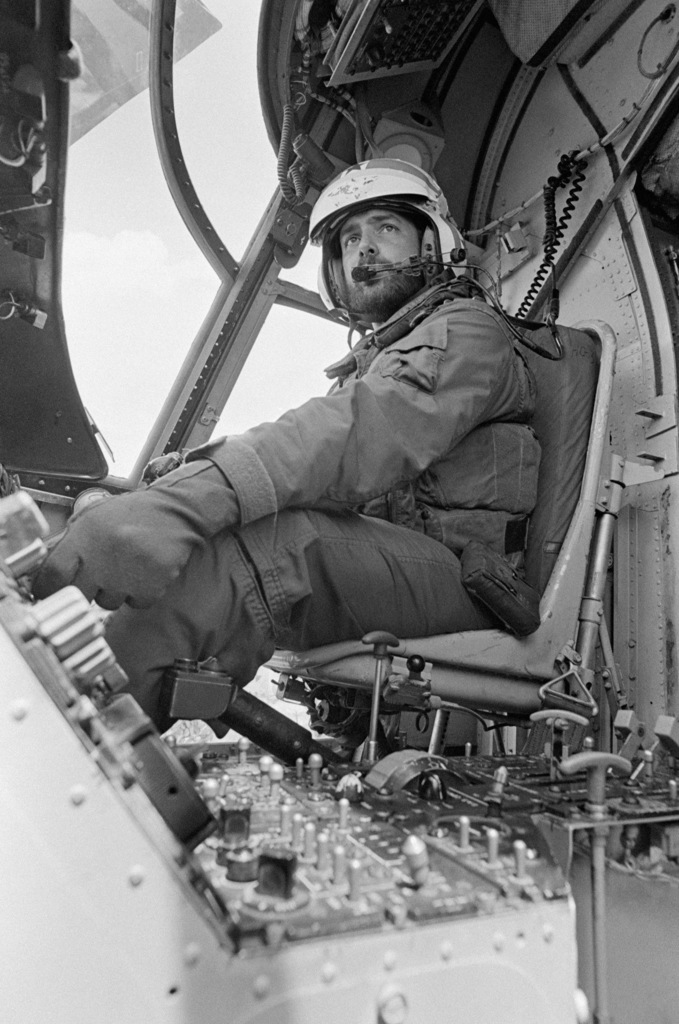 Lieutenant Junior Grade Michael G. Jegland, a pilot, in the cockpit of a CH-46 Sea Knight helicopter on the flight deck of the combat stores ship USS SAN JOSE (AFS 7)