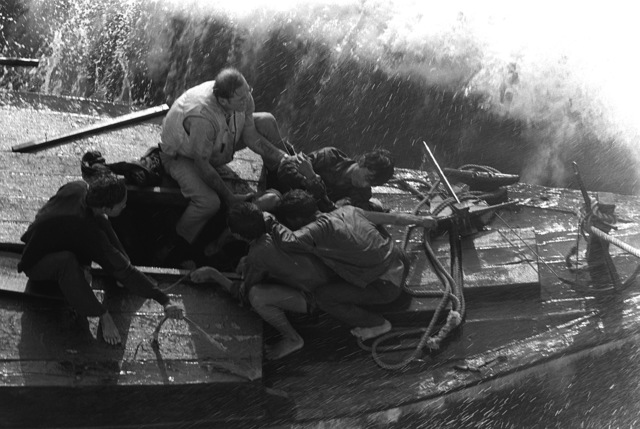 A chief boatswain's mate from the combat stores ship USS SAN JOSE (AFS-7) helps Vietnamese refugees maneuver their fishing boat alongside the ship. Fifty-five refugees were rescued by the SAN JOSE