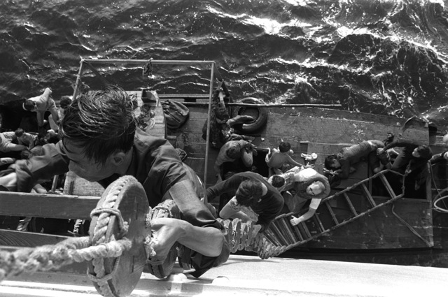 A crewman from the combat stores ship USS SAN JOSE (AFS-7) helps Vietnamese refugees climb from their fishing boat up a Jacobs ladder to the deck of the ship. Fifty-five refugees were rescued
