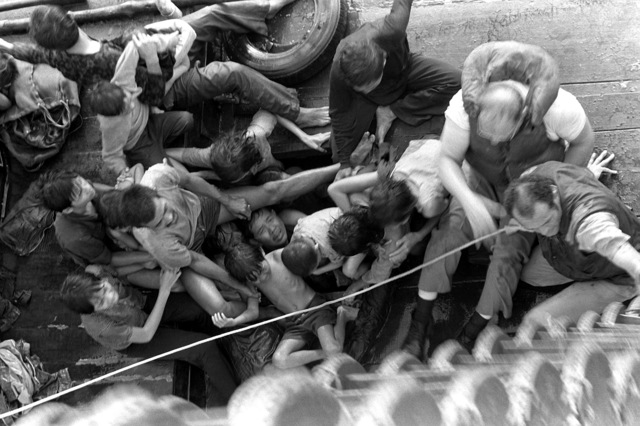 A view looking down into the fishing boat carrying 55 Vietnamese refugees as it is maneuvered alongside the combat stores ship USS SAN JOSE (AFS-7) during rescue efforts