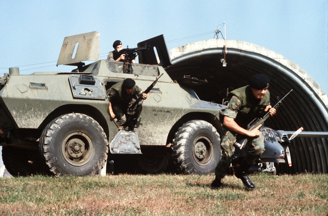 Security policemen leave an armored personnel carrier on the run to defend an OV-10 Bronco aircraft during an operational readiness inspection. The policemen are from the 51st Security Police Squadron. Bi-monthly Aerospace Audio Visual Service PHOTO Contest, B&W Entry, Jul. 1980
