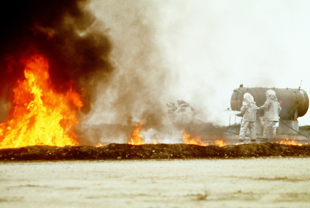 """Air Force firemen battle an """"aircraft crash"""" fire during training. This exercise is part of joint-community wilderness, structure and oil field fire training"""