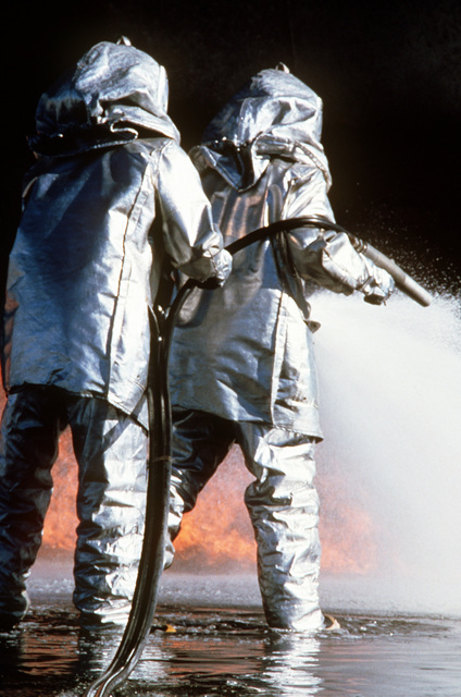 "Air Force firemen spray foam to extinguish an ""aircraft crash"" fire during training. This exercise is part of joint-community wilderness, structure and oil field fire training"