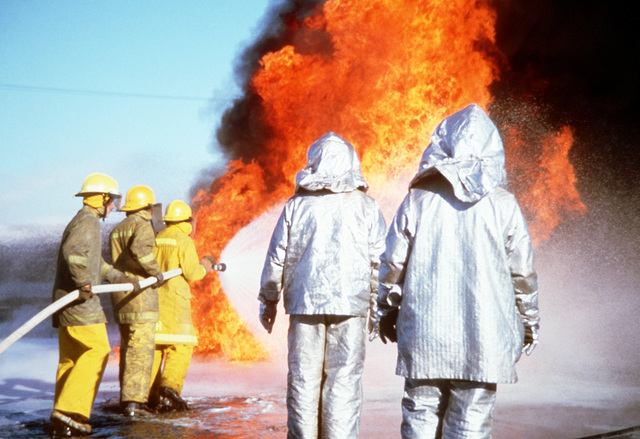 """Lompoc City firemen battle an """"aircraft crash"""" fire as Air Force firemen watch during training. This exercise is part of joint-community wilderness, structure and oil field fire training"""