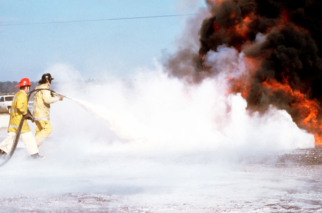 """Santa Barbara County firemen spray foam to extinguish an """"aircraft crash"""" fire during training. This exercise is part of joint-community wilderness, structure and oil field fire training"""