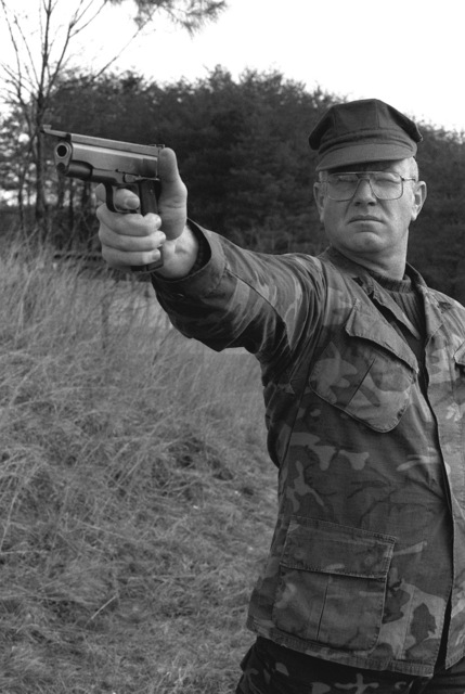 MGYSGT Vernon Zuleger, non-commissioned officer in charge of the Marine Corps Rifle Team, Weapons Training Battalion, aims his COL .45 pistol during target practice at the Marine Corps Development and Education Command