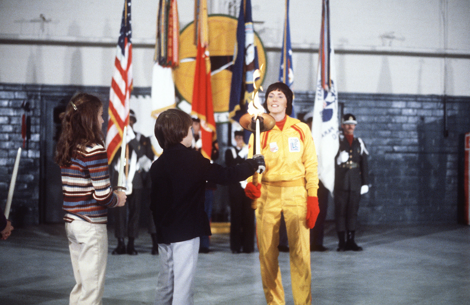 First Olympic torchbearer Sandy Norris, after her relay, lights children's candles from the flame at the flame arrival ceremony. The flame, first ignited in Olympia, Greece, is carried in a series of 52 torchbearers in a 1,000-mile run from the base to Lake Placid, New York, to open the XIII Winter Olympics