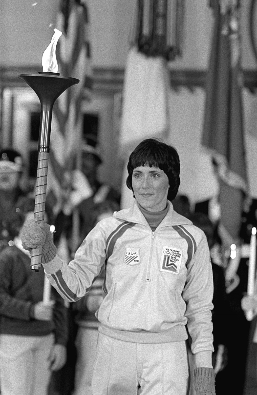 First Olympic torchbearer Sandy Norris, after her relay, stands at attention at the flame arrival ceremony. The flame, first ignited in Olympia, Greece, is carried in a series of 52 torchbearers in a 1,000-mile relay run from the base to Lake Placid, New York, to open the XIII Winter Olympics