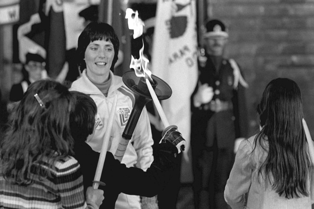 First Olympic torchbearer Sandy Norris, after her relay, stands at attention at the flame arrival ceremony. The flame, first ignited in Olympia, Greece, is carried in a series of 52 torchbearers in a 1,000-mile relay run from the base to Lake Placid, N.Y., to open the XIII Winger Olympics