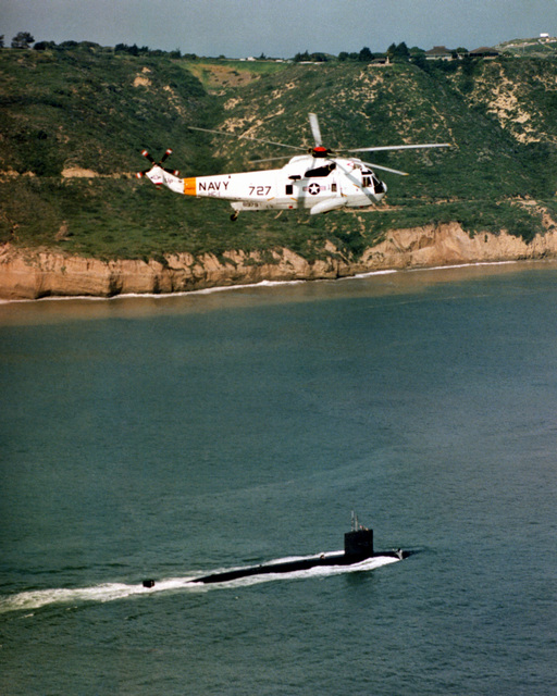 An air-to-air right side view of an SH-3 Sea King helicopter in-flight over a nuclear-powered submarine off the coast