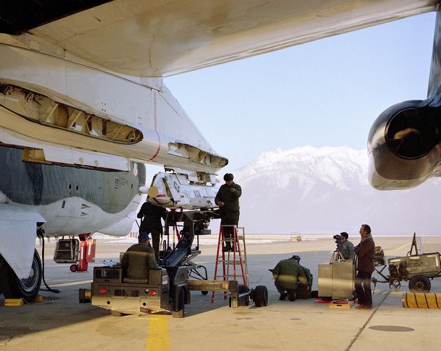 A ground crew loads an AGM-86 air-launched cruise missile on a B-52 Stratofortress aircraft wing pylon for an icing test mission