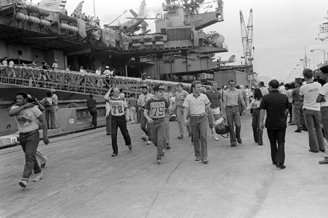 Crewmen walk along the pier looking for family and friends, after returning from an Indian Ocean deployment aboard the aircraft carrier USS MIDWAY (CV 41)