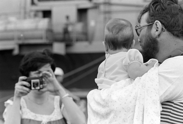 PETTY Officer 2nd Class (PO2) Robert Stollen holds his daughter for the first time as he returns from an Indian Ocean deployment aboard the aircraft carrier USS MIDWAY (CV 41)