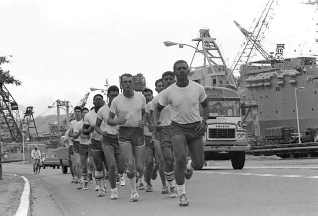 A squad of Marines from the 31st Marine Amphibious Unit jog on the pier, soon after their arrival. The Marines are stationed aboard the USS SAN BERNARDINO (LST-1189) and are a part of the 1ST Marine Division located in Hawaii