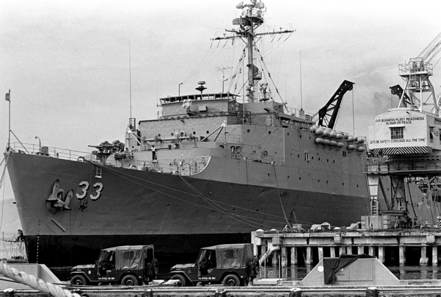 Tied up at the dock is the dock landing ship USS ALAMO (LSD-33)
