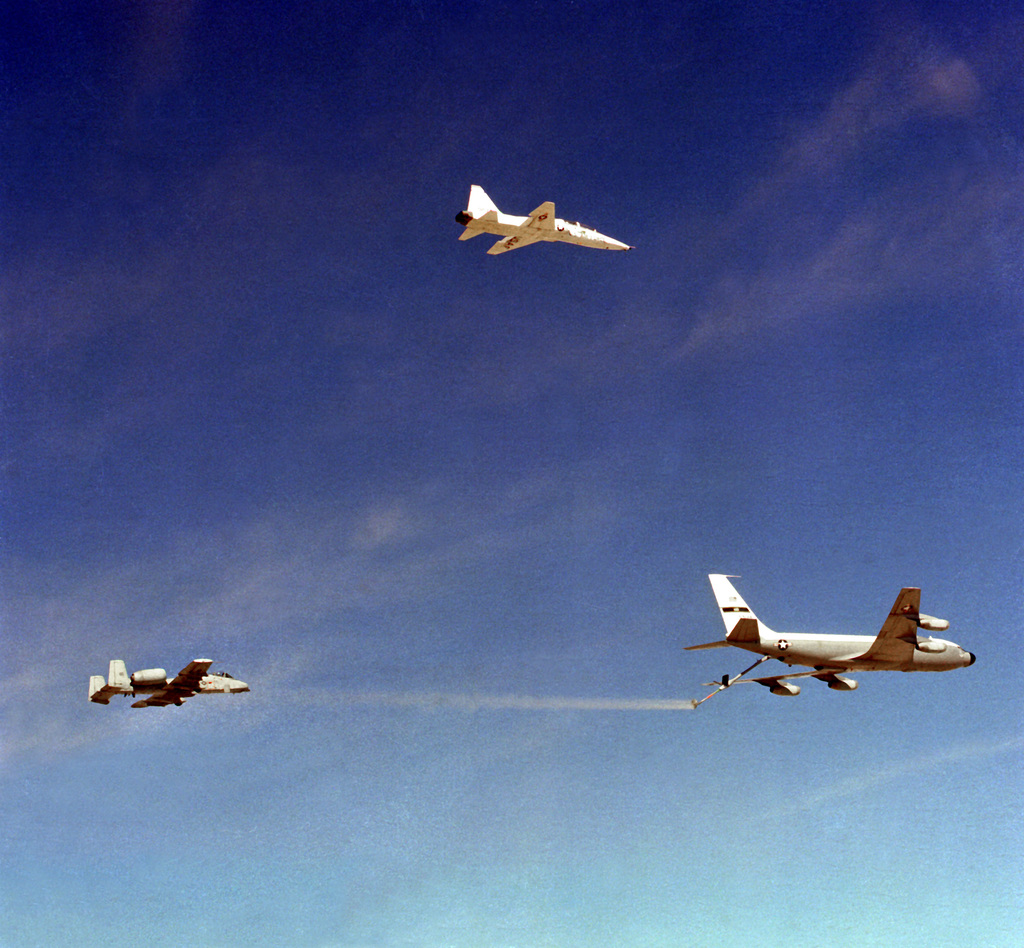 An A-10 Thunderbolt II aircraft, left, and KC-135 Stratotanker aircraft participate in an icing test while a T-38 Talon aircraft, top, acts as a photo chase plane