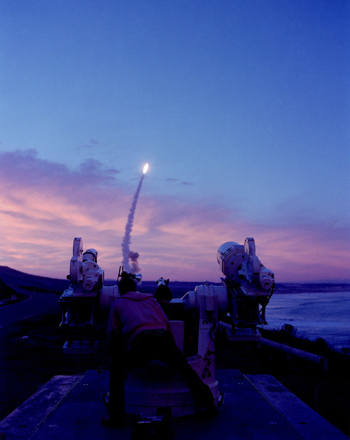 "AN LGM-30G Minuteman III missile is being launched at dawn as a photographer in the foreground operates motion picture equipment to document the launch. Bi-monthly Aerospace Audio Visual Service photo contest, color entry, July 1980, ""Minuteman Launch at Dawn."""