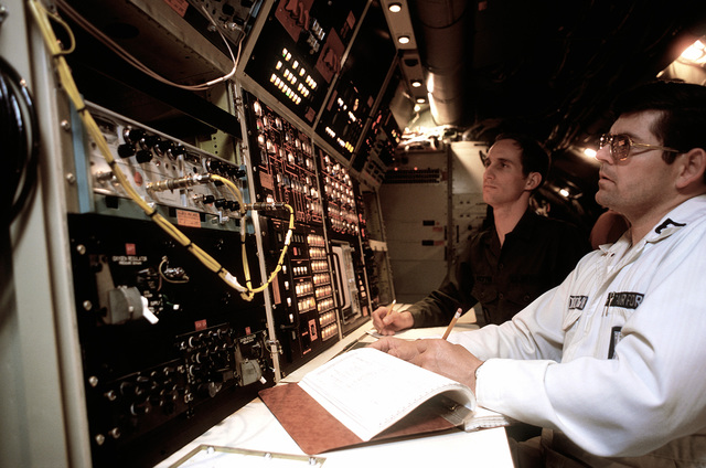 CPT Criag Weston (left), gas dynamic laser engineer, and CPT Richard Underdown, electrical systems engineer, preflight and gas dynamics laser control panel aboard the airborne laser laboratory