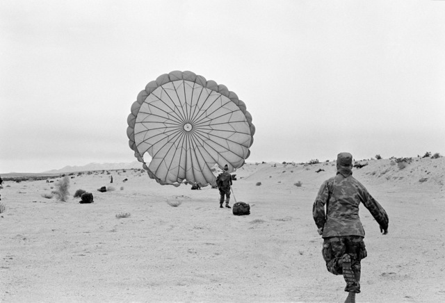 An Army parachutist from 3rd Battalion, 5th Special Forces, Georgia, is the first soldier to land to participate in Operation GABLIN WATER. A Marine runs to give the soldier assistance
